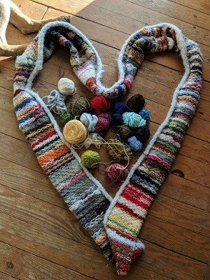 An infinity scarf made from scrap yarn pictured in the shape of heart, with small remnants of yarn in the middle and two dog legs in the upper corner.